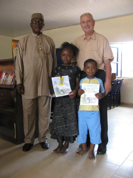 With the school headmaster and two of the children, at a local school where Allyn donated books and crayons