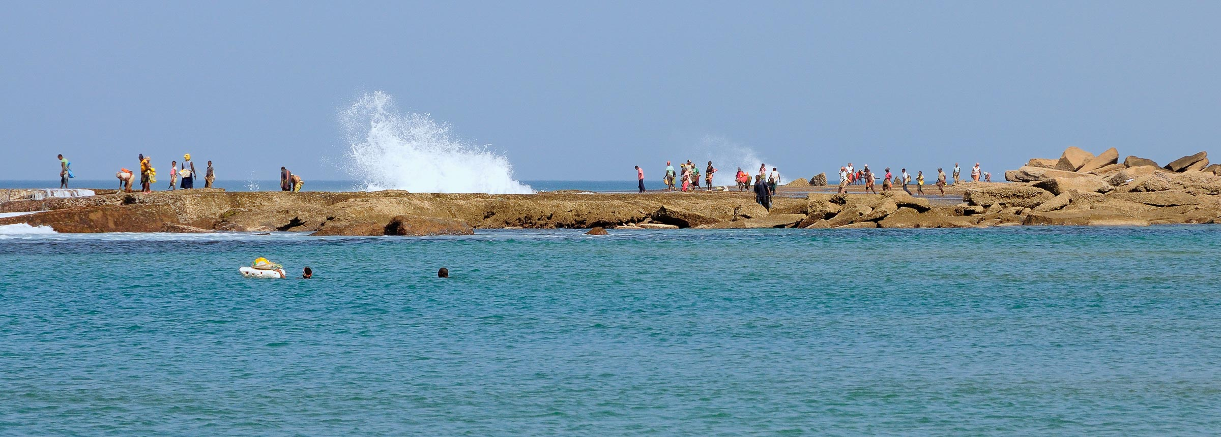 Locals harvesting shellfish from rocks at Xai Xai beach