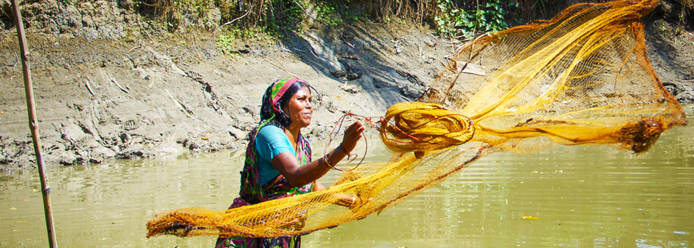 Bangladeshi woman casting fishing net