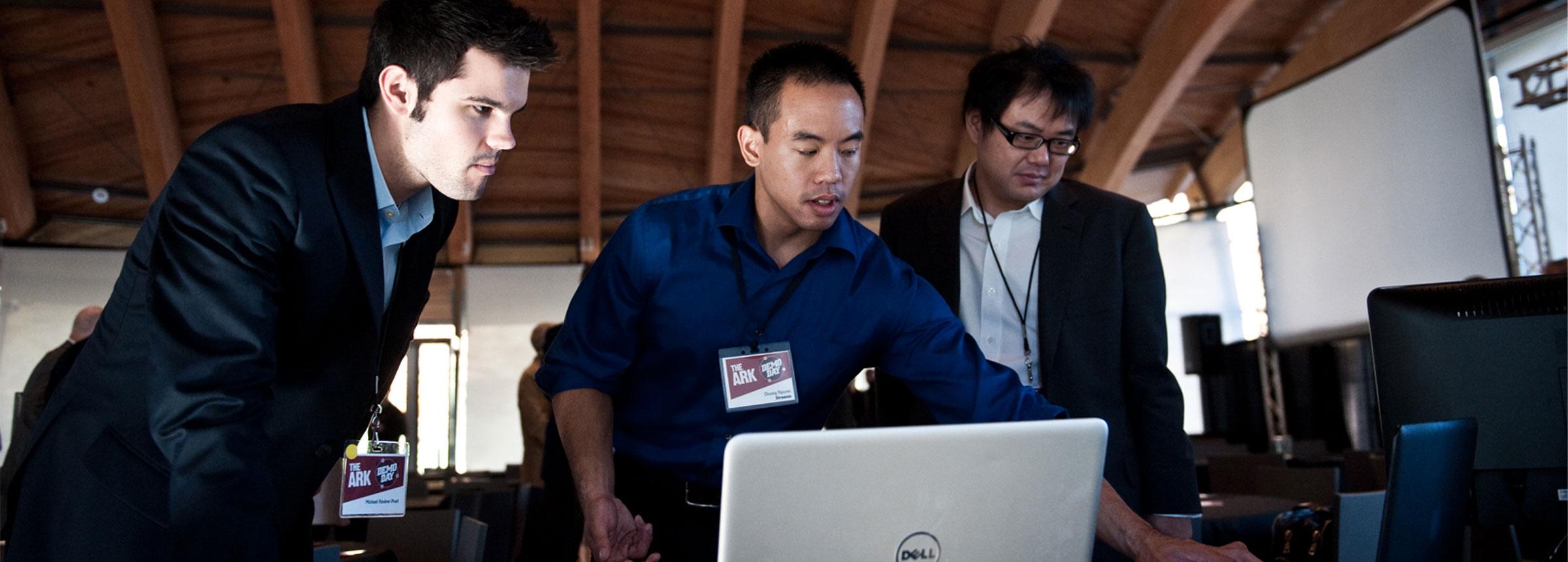 Three men huddled around laptop