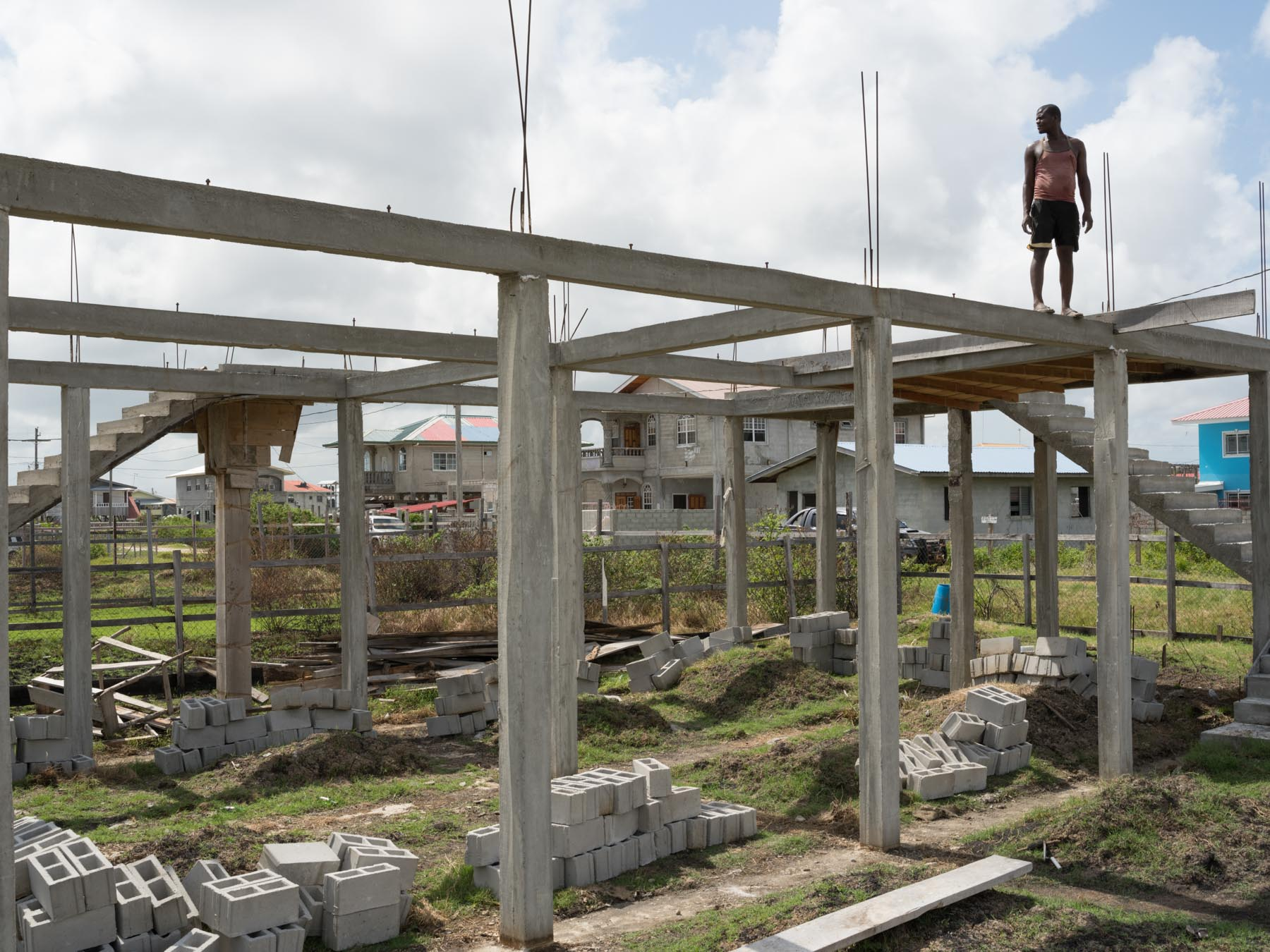 Near the sea wall in Georgetown, houses are built on stilts. The stilts protect residents from wild animals, and from high tides that crest over the flood walls. Orrin Harcourt builds a house near the coast, with the help of his son Leyland. (Photo: Lucas Foglia)