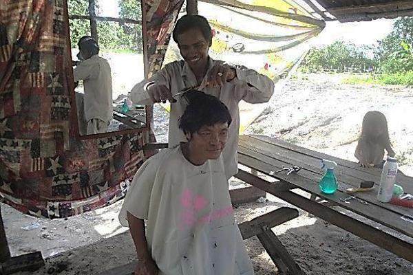 A man cuts a customer's hair.
