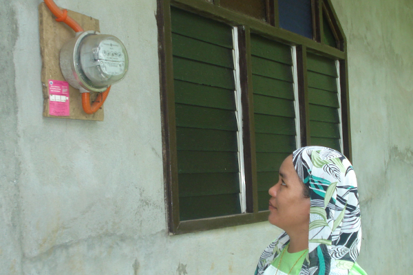 Bai Aniza checks an electric meter.