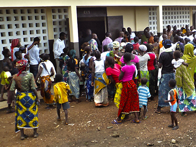 A crowd gathers around a school in Côte d'Ivoire.