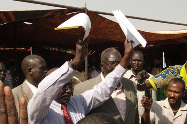 Governor Paul Malong displays a joint communiqué between the Dinka Malual and Rezeigat to a crowd gathered in Aweil.