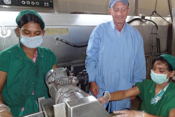 Volunteer Cliff Wener trains factory staff on new ways to prepare food.