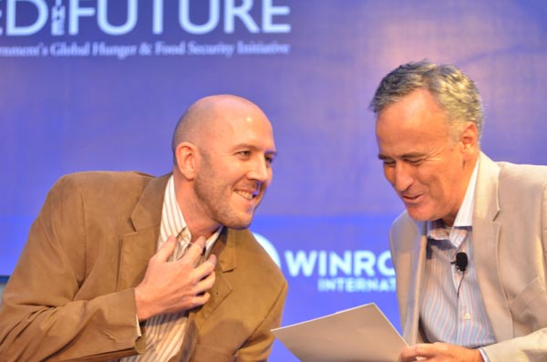Kipp Sutton of USAID and Rob Turner of Winrock International share a laugh from the stage.
