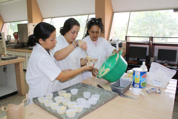 Volunteer Eliana Pinilla demonstrates sorghum processing techniques