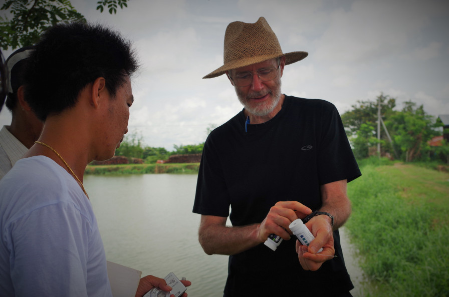 Dr. Hugh Thomford shows workers how to properly use testing stripes to check pH levels in the ponds