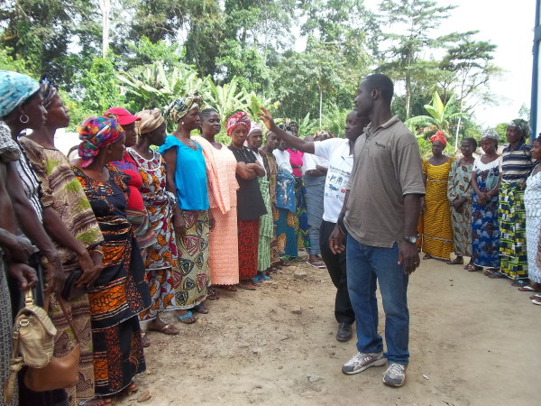 "Agronomist Sylvester Kpai, Sr. and Sam Zourpeawon, secretary for the Gbehlay Geh Rural Women's structure, lead an ""ice breaker"" exercise with workshop participants"