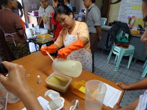 participant pouring oil into caustic solution