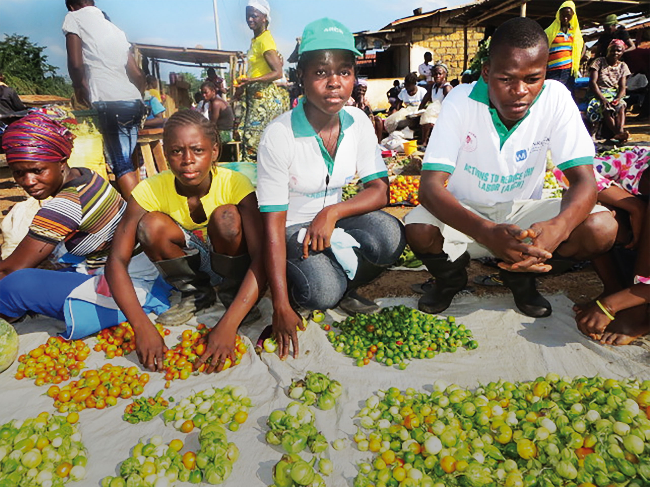 Mercy Dahn, second from right, and other students display their produce at a local market in Karnwee, Liberia.